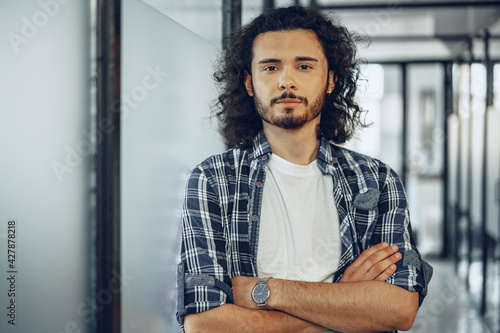 Photo Portrait of young curly casually dressed male entrepreneur standing in a glass c