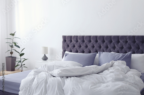 Modern bed with crumpled blanket and pillows indoors - fototapety na wymiar