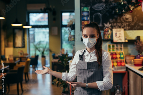 Fotografie, Obraz waitress with face mask welcome to restaurant