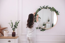 Woman Decorating Mirror With Eucalyptus Branches At Home
