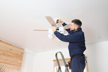 Electrician With Screwdriver Repairing Ceiling Fan Indoors. Space For Text
