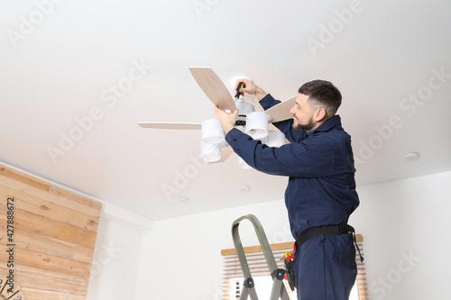 Electrician with screwdriver repairing ceiling fan indoors Tapéta, Fotótapéta