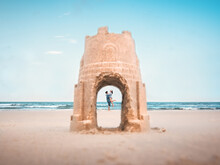 Man Lifting Woman Seen Through Hole In Sandcastle At Beach Against Sky