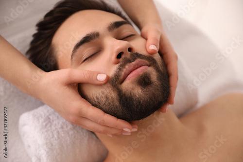 Obraz Young man receiving facial massage in beauty salon, closeup - fototapety do salonu