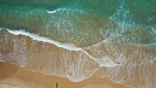 Aerial View Of The Wavy Ocean Hitting The Sandy Beach On The Coast