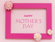 Creative Arrangement Of Flowers On Pink Background With Happy Mothers Day Text. Flat Lay.