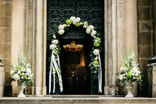 Church Door Decorated With Beautiful White Flowers And Ribbons During Wedding Ceremony