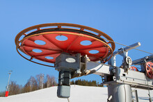 Large Spinning Wheel With Electric Cable Hoist Motor In A Ski Resort. The Drive Mechanism Against The Blue Sky. Mountain Slope Equipment For Snowboarding. Ski Tours On A Sunny Day.