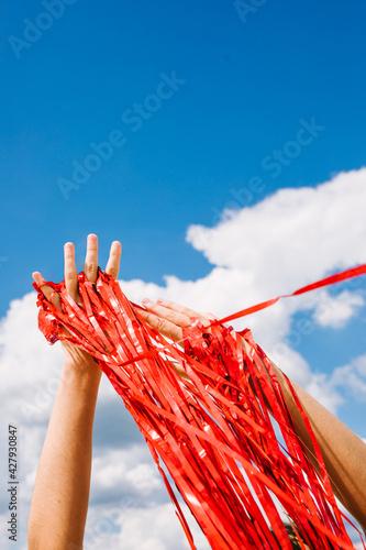 hands holding red ribbon Fototapeta