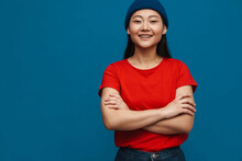 Asian Teen Girl In Hat Smiling While Posing With Arms Crossed