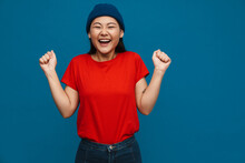 Excited Asian Teen Girl In Hat Gesturing And Laughing At Camera