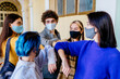 Group of five youth people wearing face masks while bumping their elbows instead of greetings in university indoor. New social rules concept. Students meeting together.
