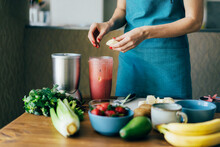 A Woman Puts The Ingredients In A Blender Bowl To Make A Spring Fruit And Berry Smoothie. Cooking At Home In The Kitchen, Care And Nutrition And Health.