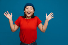 Excited Asian Teen Girl In Hat Gesturing And Smiling At Camera