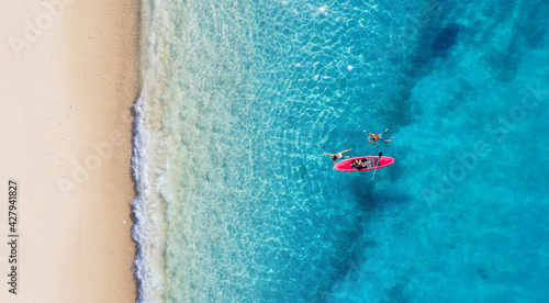 Kayaking. Sup. Aerial view of floating board and people on blue sea at sunny day. Summer seascape. Landscape from drone. Travel and active life image.