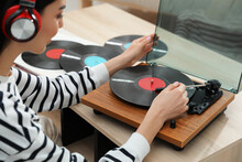 Woman Listening To Music With Turntable At Home