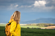 Woman Enjoying View At Rural Scenery During Spring Hike. Female Tourist With Backpack Wearing Yellow Raincoat
