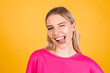 Pretty european woman in pink blouse on yellow background sticking tongue out happy with funny expression does funny grimaces