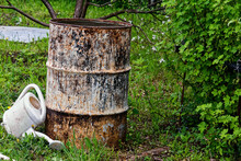 An Old Iron Barrel Stands Among The Trees