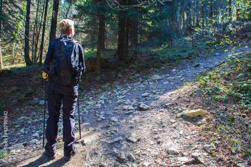 Młoda kobieta z plecakiem na spacerze w górach w słoneczny dzień - fototapety na wymiar
