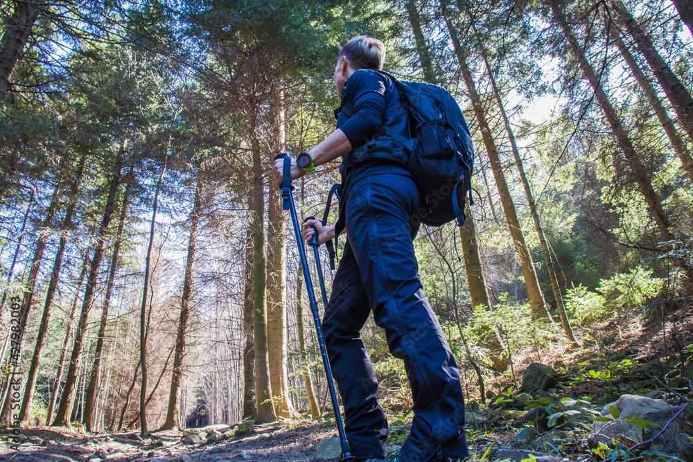 Fototapeta Młoda kobieta z plecakiem na spacerze w górach w słoneczny dzień