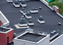 Top View Dark Flat Roof With Air Conditioners And Hydro Insulation Membranes Modern Apartment Building Residential Area.