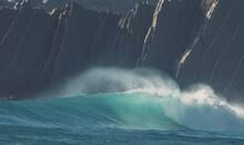 Blue Waves Crashing On The Rocks