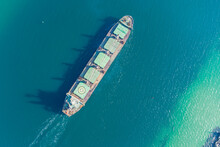 The Dry Cargo Vessel Enters The Port With The Help Of Tugs. Photo From A Helicopter. Bird's-eye View.
