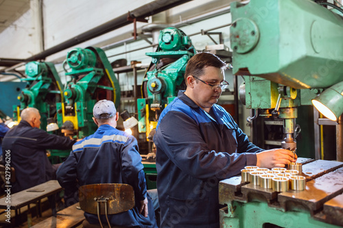 Tela Worker in production plant drilling at machine on the factory floor