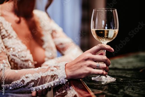 Canvas bride drinking wine on her wedding day white dress