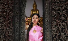 Portrait Asia Woman Dress Traditional Thai Dress Standing At Front Carved Wooden Door Of Temple Againt Buddha Status On Backgorund