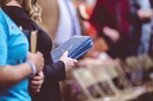 People Holding Bible Books And Praying During A Congregation