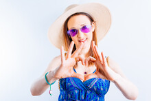 Beautiful Young Woman On White Background Making A Heart With Her Hands Dressed In Straw Hat, Dress And Purple Summer Glasses. Concept Summer Arrival Love To Summer