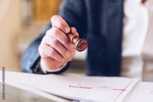 Tablou Canvas Close-up of the hand of a notary public or lawyer with an approved stamp on certificate or document public