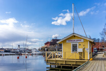 Wooden Harbor Office With Sailboats In Background