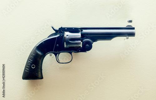 Fotografie, Obraz Revolver gun isolated on a light yellow background