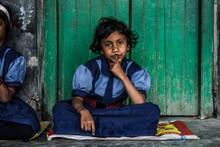 Portrait Of Girl Sitting By Wooden Door