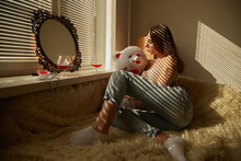 Young Woman With Teddy Bear Sitting On Bed At Home