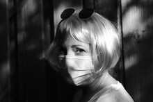 Close-up Portrait Of Woman Wearing Mask Standing Against Wall