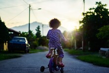Rear View Of Girl Riding Bicycle On Road
