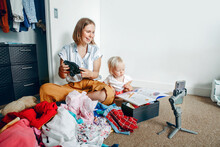 Mother  Doing Video Call Chat While Sorting Clothes At Home. Woman Using Gimbal Tripod For Video