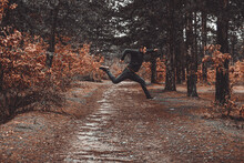 Man Jumping In Forest During Autumn