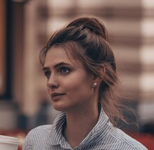Close-up Portrait Of Young Woman Looking Away Outdoors Drinking Coffe