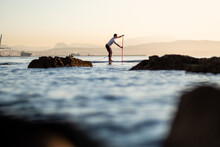 Full Length Of Man Standing On Paddleboard In Sea