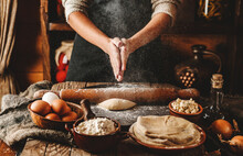 Woman Hands Cooking Dough On Rustic Wooden Background. White Flour Flying Into Air. Cooking Bread With Cheese, Eggs And Herb. Homemade Healthy Food Concept, Toning