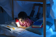 Asian Girl Child To Make A Camp To Play Imaginatively And Reading Book By Flashlight  In Living Room At Home..