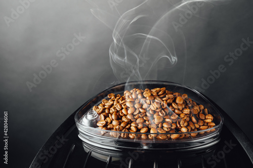 Foto fresh roasted coffee beans with smoke in coffeemaker bean container, close-up vi