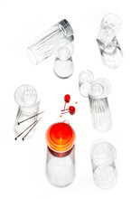 Overhead Image Of Empty Glasses On White With Strong Shadows, One Glass With Red Liquid & Cherries.