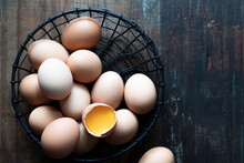 Whole Eggs And A Cracked Egg In A Wire Basket.