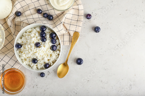Bowl of cottage cheese with blueberries on light background